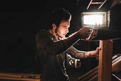 Young Man Saws Wood in Workshop - p1166m2138231 by Cavan Images