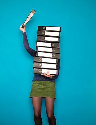 Woman with a huge pile of binders - p1231m1041944 by Iris Loonen