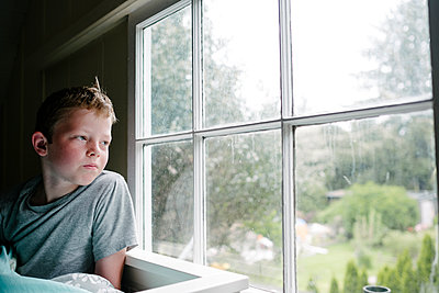 Boy looking out window - p1262m1440866 by Maryanne Gobble