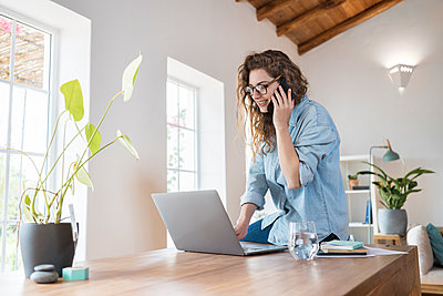 Smiling female professional talking on smart phone while working on laptop at desk - p300m2277558 by Steve Brookland