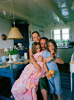 Family with two daughter hugging inside home - p528m718518f by Peter Eriksson