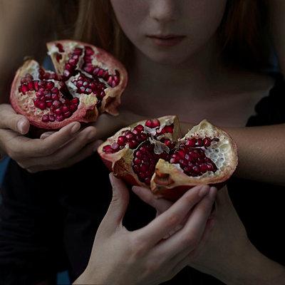 Intertwined Caucasian girls holding sliced pomegranate - p555m1303330 by Vladimir Serov