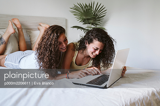 Happy lesbian young couple using laptop while lying on bed at home - p300m2206611 by Eva Blanco