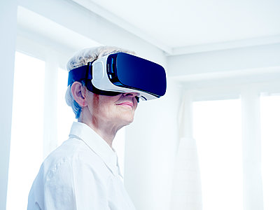Senior woman wearing Virtual Reality Glasses - p300m1153675 by Dieter Schewig