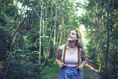 Portrait of smiling young woman with backpack in forest watching something - p300m2166267 by Bernd Friedel