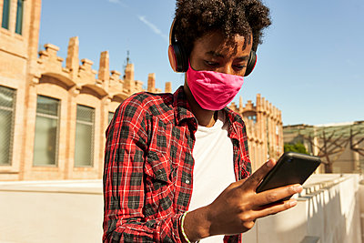Afro young woman wearing pink sanitary mask while using smart phone during COVID-19 - p300m2241785 by Veam