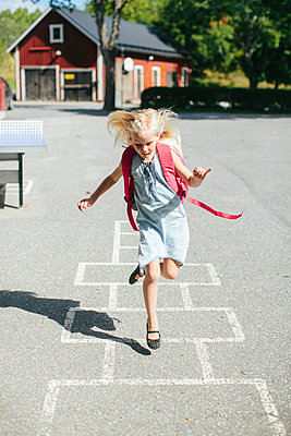 Girl playing hopscotch - p312m1228925 by Anna Rostrom