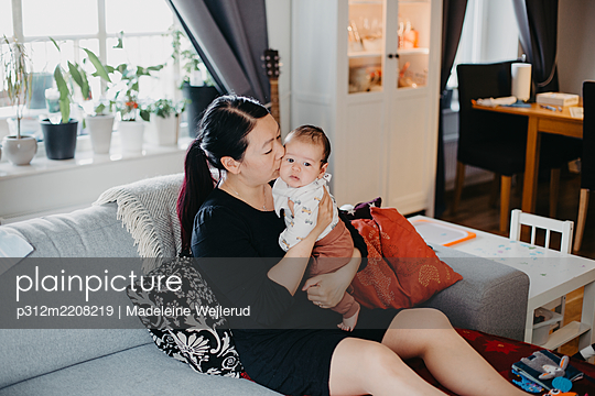 Woman sitting with baby on sofa - p312m2208219 by Madeleine Wejlerud