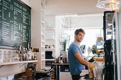 Portrait of smiling man in a cafe - p300m1588136 von Kniel Synnatzschke