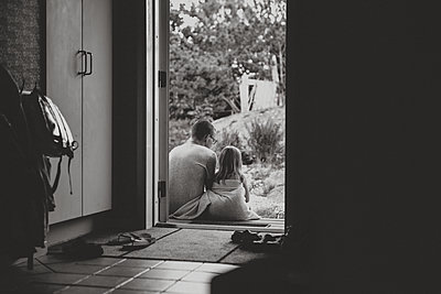 Father and daughter sitting at doorstep - p312m2139195 by Anna Johnsson