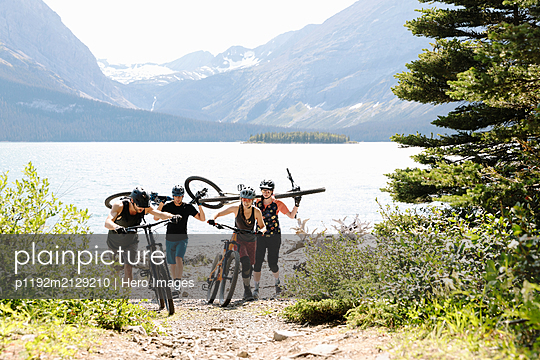 Friends mountain biking on trail at sunny lakeside - p1192m2129210 by Hero Images