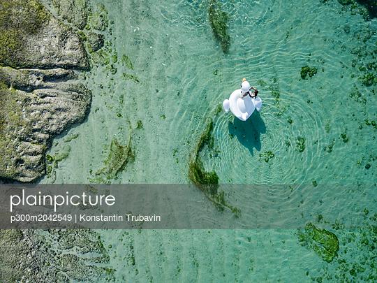Indonesia, Bali, Aerial view of Karma Kandara beach, one woman, airbed floating on water - p300m2042549 von Konstantin Trubavin