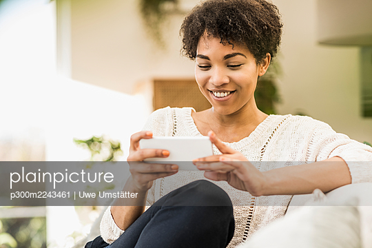 Smiling woman using mobile phone while sitting at home - p300m2243461 by Uwe Umstätter