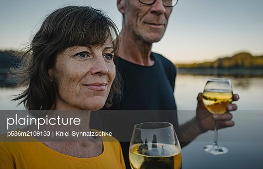 Mature couple drinking white wine at Lake Baldeneysee - p586m2109133 by Kniel Synnatzschke