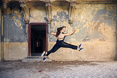 Ballet dancers leaping while dancing together in old building - p1166m2024695 by Cavan Images