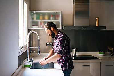 Man with beard and plaid shirt washing dishes at home. - p1166m2095954 by Cavan Images
