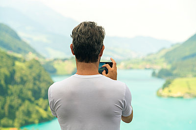 A man taking image of the Lungerersee - p1332m1488320 by Tamboly