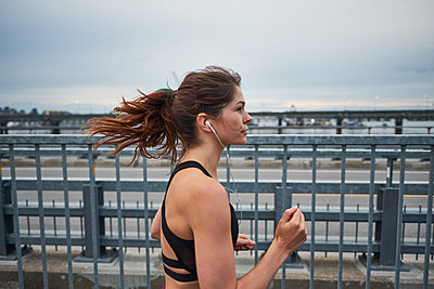 Confident woman running while training on bridge, Montreal, Quebec, Canada - p1362m1530067 by Charles Knox