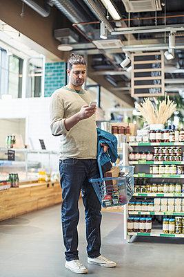 Full length of man using smart phone supermarket - p426m1407387 by Kentaroo Tryman