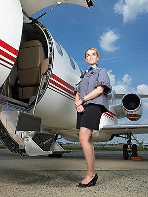 Air hostess beside private jet. - p4290624f by Ghislain & Marie David de Lossy