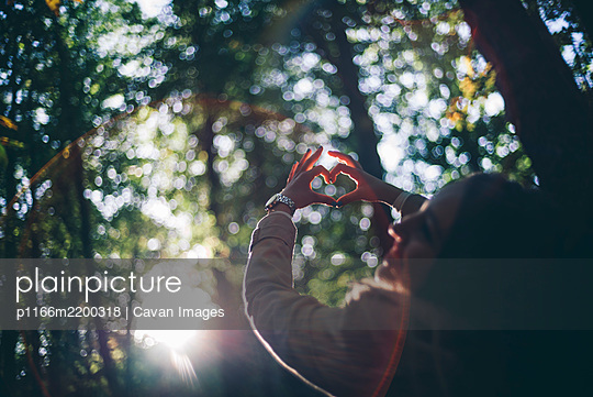 Pretty girl poses in nature makes heart with hands - p1166m2200318 by Cavan Images