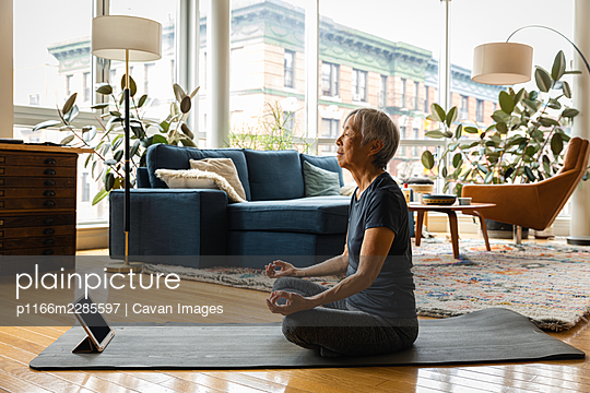Senior woman meditating while learning through digital tablet in living room at home - p1166m2285597 by Cavan Images