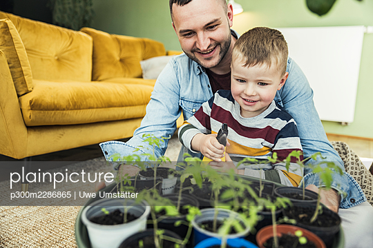 Cute boy spraying water on potted plants while sitting with father in living room at home - p300m2286865 by Uwe Umstätter