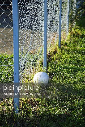 Soccer Ball Lying Next To A Chainlink Fence