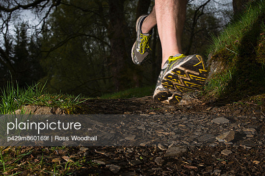 Man wearing trainers running;  close up - p429m860169f by Ross Woodhall