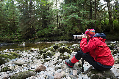 Female photographer with digital camera and lens photographing on rocks along wilderness stream - p1192m1529818 by Hero Images