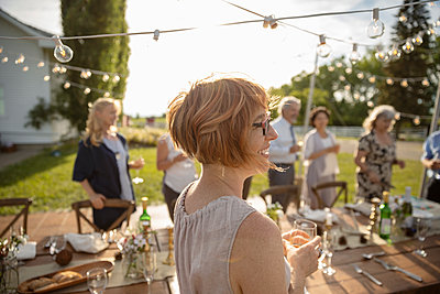 Smiling woman drinking wine at sunny rural garden party - p1192m2009174 by Hero Images