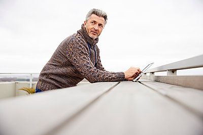 Mature man using digital tablet while standing at rooftop - p300m2242856 by Jo Kirchherr