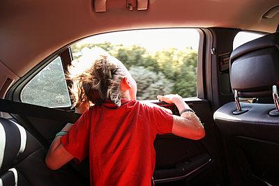 Boy looking through car window - p312m1495771 by Susanne Kronholm