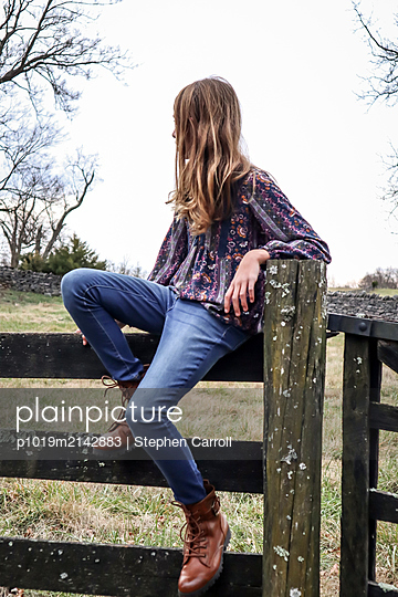 Girl sitting on wooden fence - p1019m2142883 by Stephen Carroll