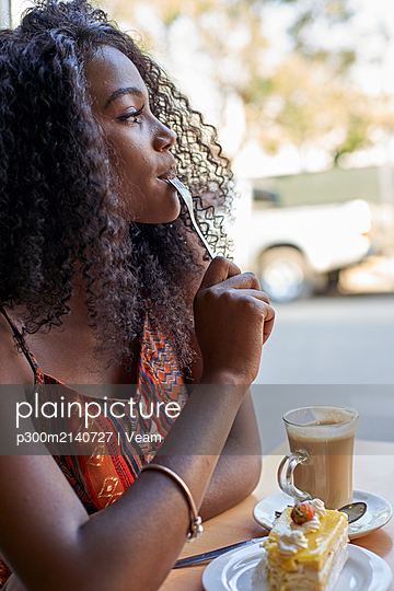 Portrait of young African woman eating a piece of cake and having a coffee - p300m2140727 by Veam