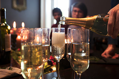 Close-up of man pouring champagne in glasses during Christmas party - p1166m1087914f by Lumina Images
