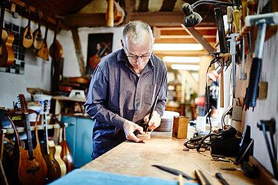 Gitarrenbauer arbeitet in seiner Werkstatt - p1359m1221836 von Great Images
