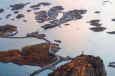 Norway, Lofoten Islands, Henningsvaer, man standing on viewing point with raising arms - p300m2104531 by Valentin Weinhäupl