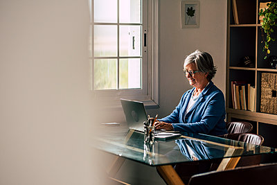 Smiling senior female entrepreneur with laptop working from home - p300m2277630 by Simona Pilolla
