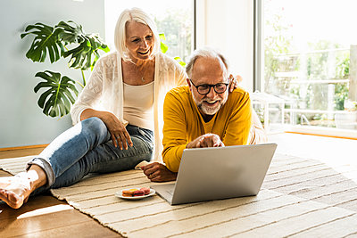 Mature couple using laptop at home - p300m2293804 by Uwe Umstätter