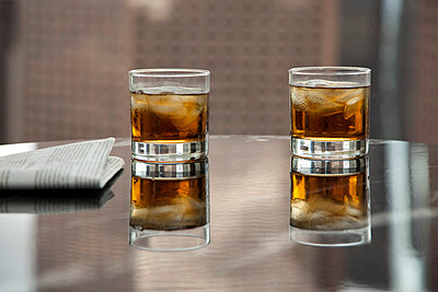 Two glasses of whiskey and ice on a table - p30117838f by Antenna photography