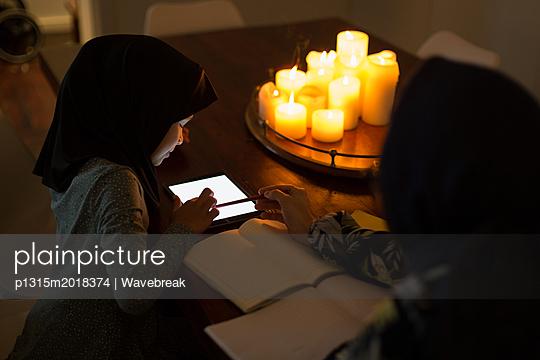Muslim woman helping her daughter with homework - p1315m2018374 by Wavebreak
