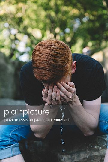 Mann im Park sein Gesicht waschend - p1491m1582703 von Jessica Prautzsch