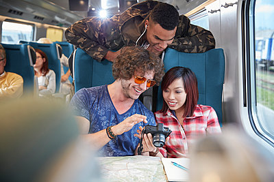 Young friends looking at photographs on digital camera on passenger train - p1023m1561156 by Agnieszka Olek