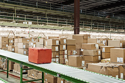 Conveyor belt system and cardboard boxes of products in a distribution warehouse. - p1100m2002288 by Mint Images