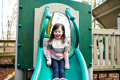 young girl enjoying slide at the playground. - p1166m2163391 by Cavan Images