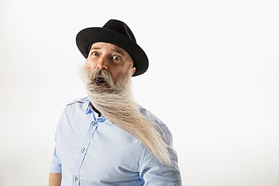Portrait surprised hipster with wind blowing beard against white background - p1192m1230962 by Hero Images