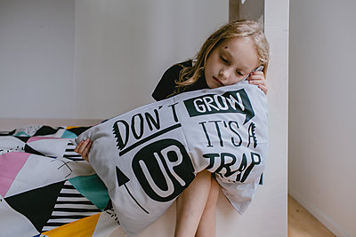 Sad girl sitting on bed - p1414m2044873 by Dasha Pears