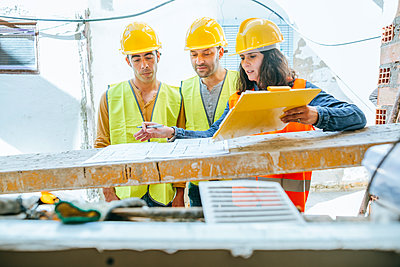Woman talking to two construction workers on construction site - p300m1356303 by Kiko Jimenez