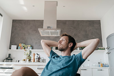 Pensive man with hands behind head sitting in the kitchen looking at distance - p300m1550236 by Kniel Synnatzschke